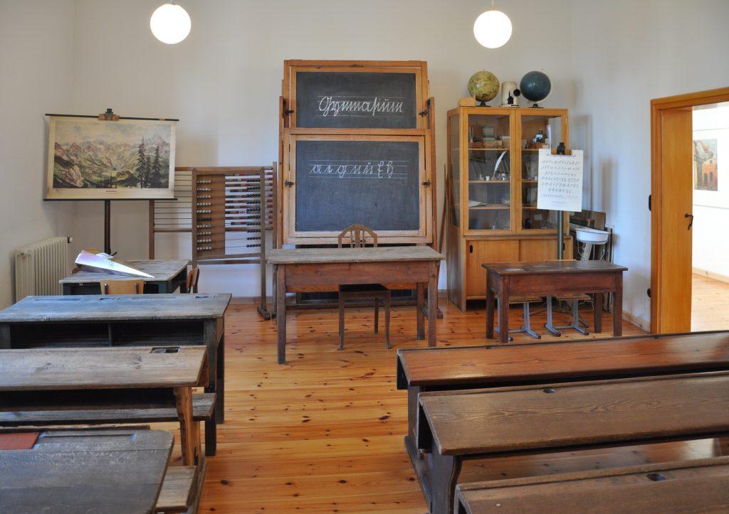 Foto eines historischen Klassenzimmers mit Holzmöbeln und Kreidetafel