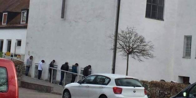 Fünf Personen lehnen an einer Wand